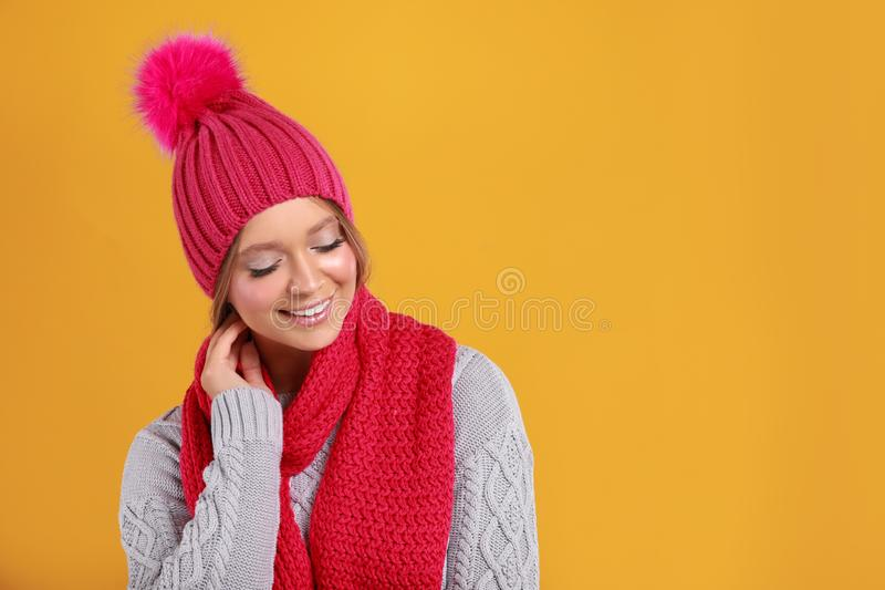 Young woman in warm sweater, scarf and hat on yellow background, space for text. Winter season royalty free stock photography