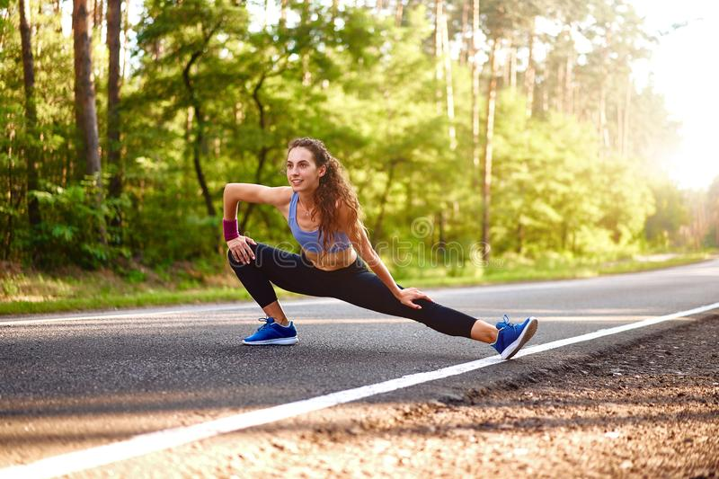 Young woman warming up at forest road before jogging. Attractive girl stretching for running exercises. Beautiful curly sporty stock photos