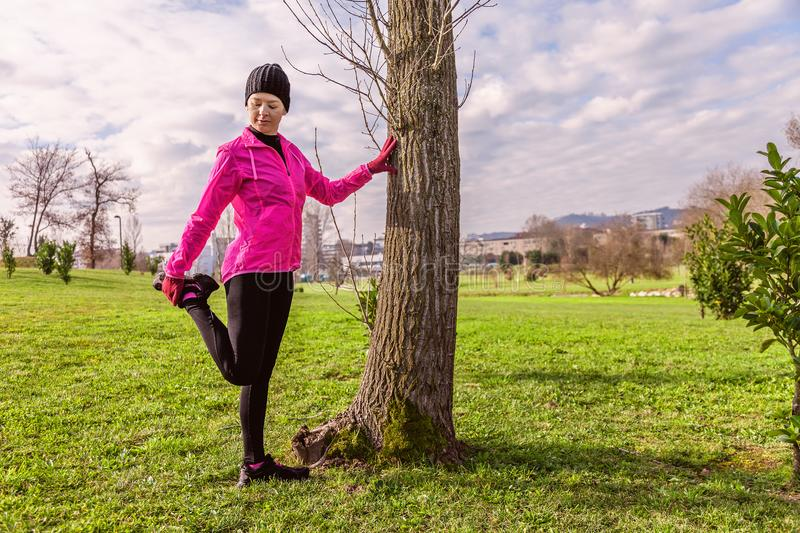 Young woman warming up and stretching the legs before running on a cold winter, autumn of fall day in an urban park. royalty free stock images