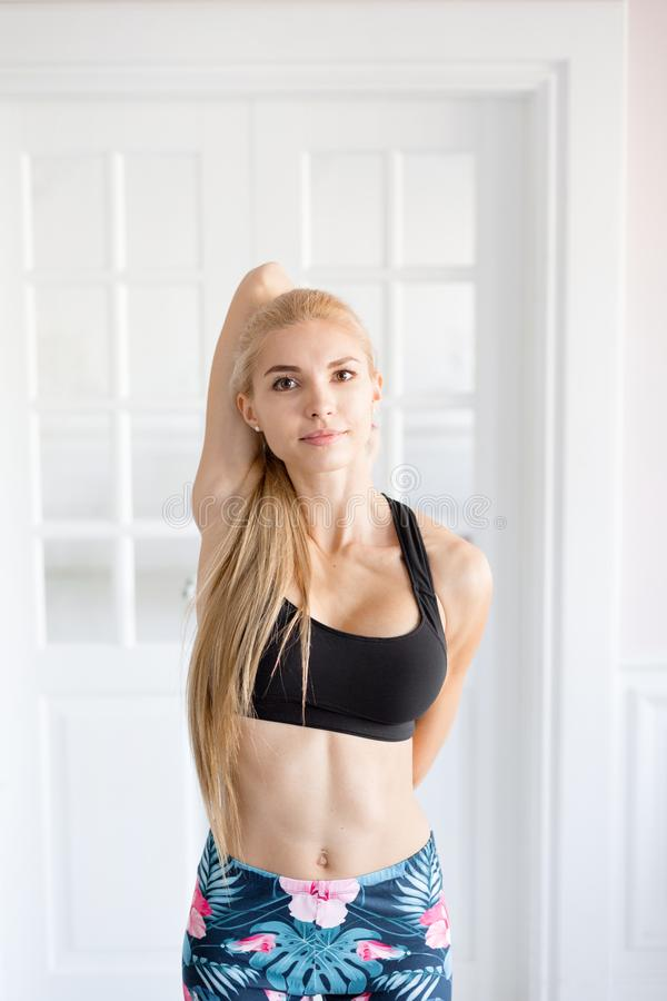 Home fitness. Young woman warming up before training doing exercises to stretch her muscles and joints. Lovely young. Young woman warming up before training stock photos