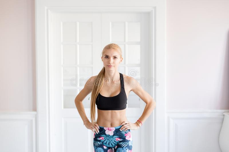 Home fitness. Young woman warming up before training doing exercises to stretch her muscles and joints. Young woman warming up before training doing exercises to stock images