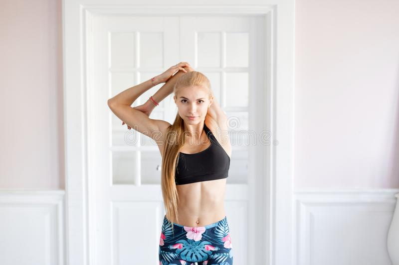 Home fitness. Young woman warming up before training doing exercises to stretch her muscles and joints. Young woman warming up before training doing exercises to royalty free stock image