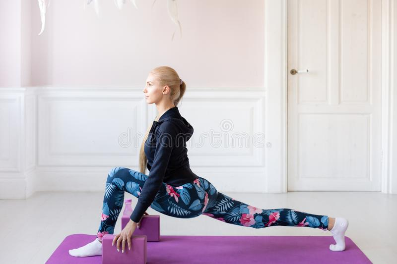 Lovely young blonde girl. home fitness. Young woman warming up before training doing exercises to stretch her muscles. Young woman warming up before training royalty free stock photos