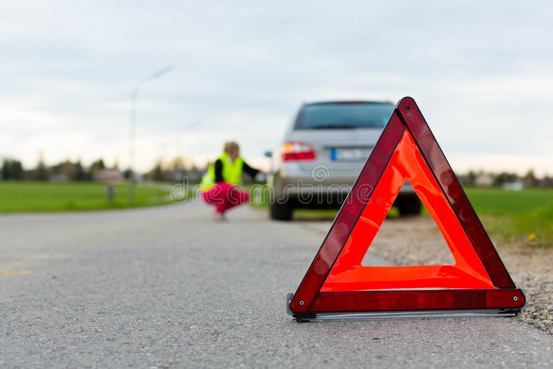 Download Young Woman With Warning Triangle On Street Stock Image - Image: 26005905