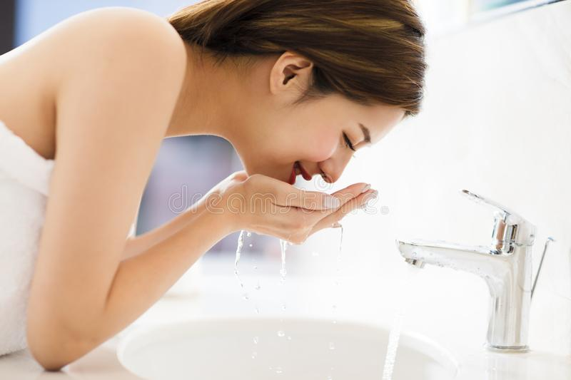 Woman washing face with clean water in bathroom royalty free stock photos