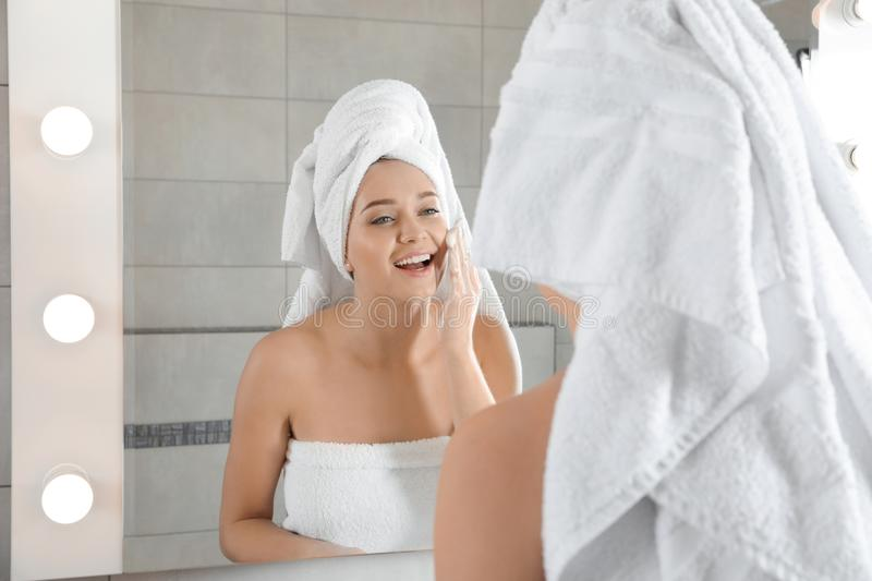 Young woman washing face with soap near mirror royalty free stock images
