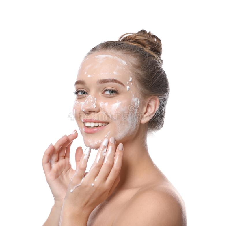 Young woman washing face with soap stock photo