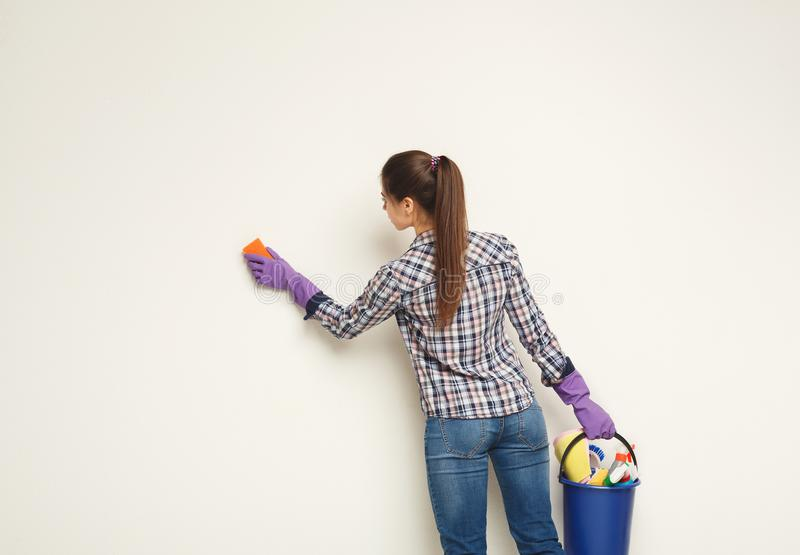 Young woman washing wall with sponge royalty free stock photos