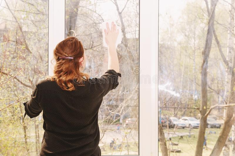 Young woman washing windows stock photography