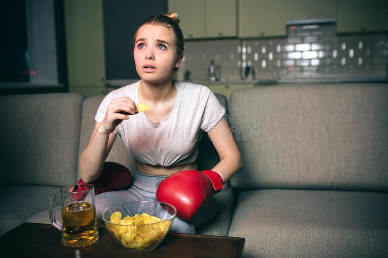 Young woman watch boxing on tv at night. Amazed blonde look up and eat junk food. Watching streaming show. Wear red stock photo