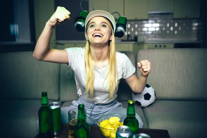 Young woman watch football game on tv at night. Blonde model look up and smile. Streaming match on tv. Beer bottles on. Table. Darkness in room royalty free stock photos