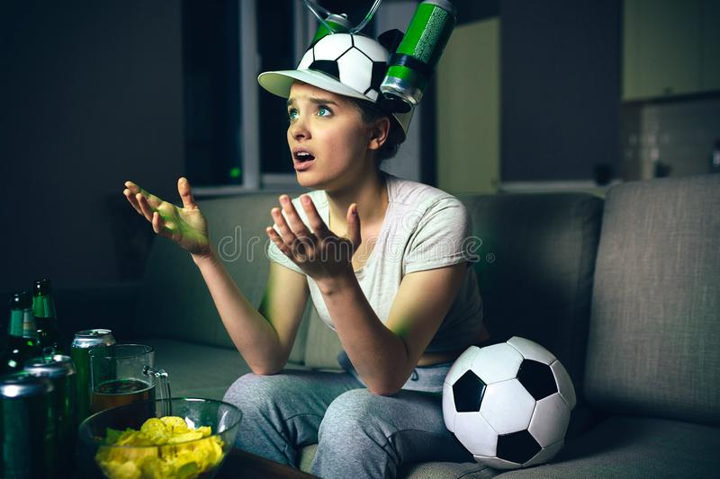 Young woman watch football game on tv at night. Confused upset model looking forward. Watching streaming match. Alone in. Dark room stock image