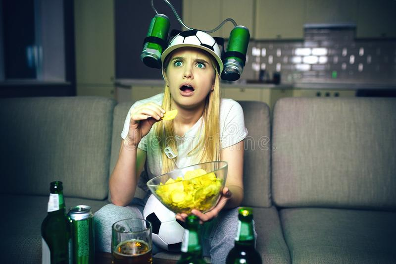 Young woman watch football game on tv at night. Worry model look up and eat chips. Blonde model wear hat with two beer. Cans on side of it. Bottle of alcohol on stock photo