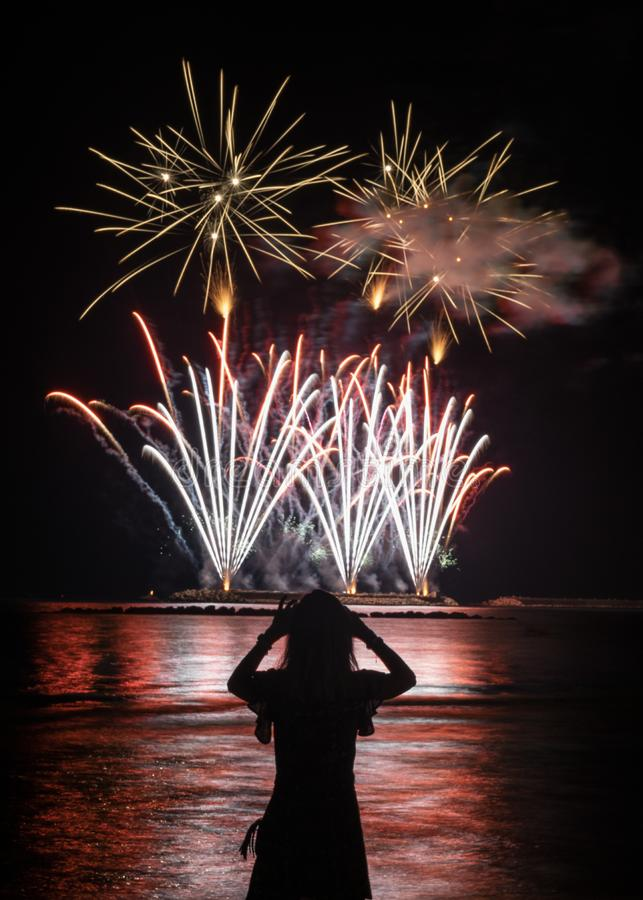 Young woman watches fireworks by the sea stock images
