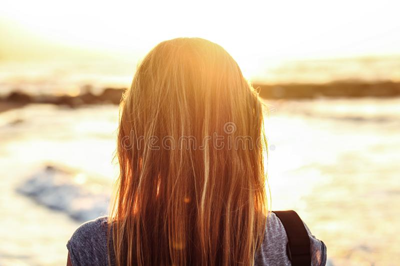 Young woman watches over sea during sunset. View from back, detail on only her hairs stock image
