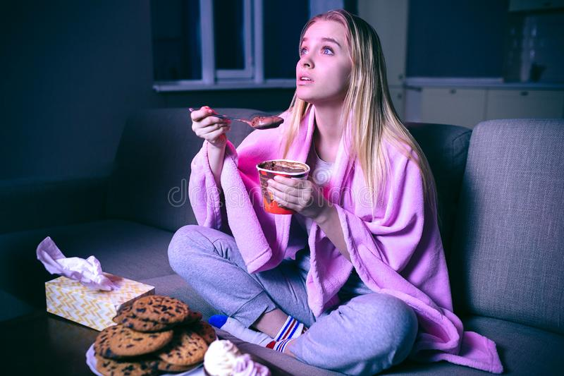 Young woman watching movie at night. Eating ice cream or chocolate with spoon. Cookies on table. Streaming show on tv. royalty free stock images