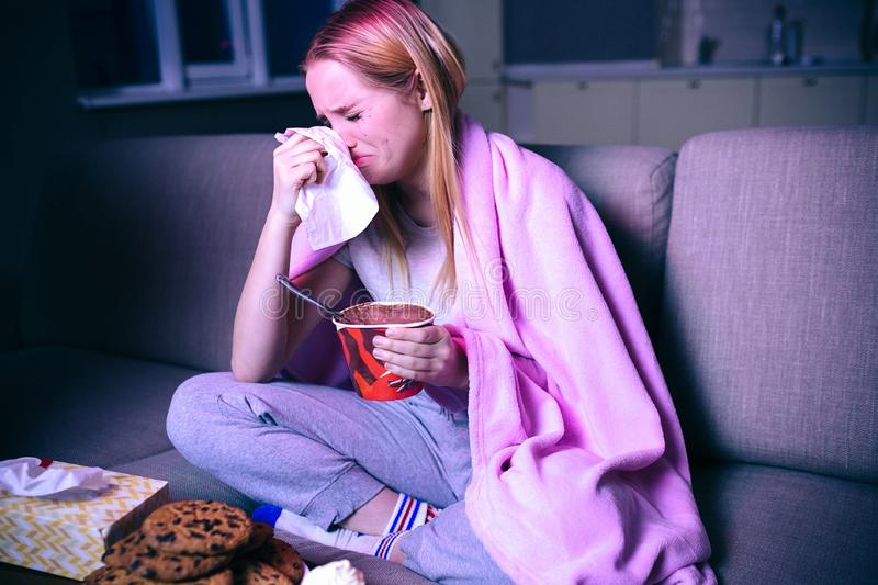 Young Woman Watching Movie At Night Sitting On Sofa And Crying