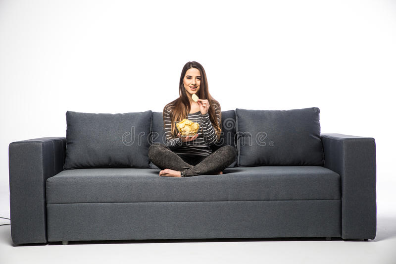 Young woman watching TV and eating chips sitting on sofa stock photo