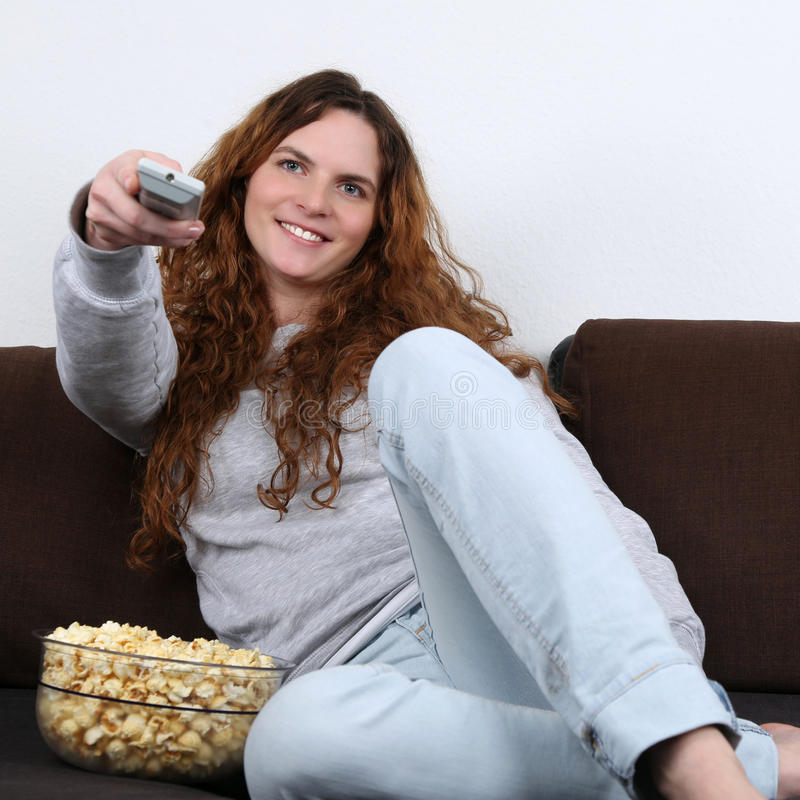 Young Woman Watching Tv And Eating Popcorn Royalty Free Stock Image
