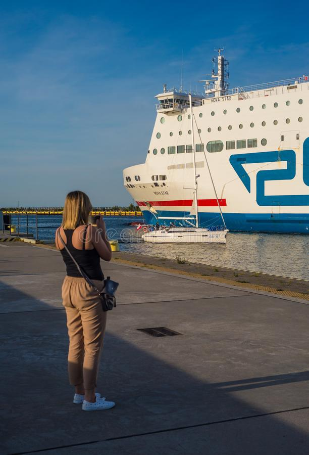 Young woman watching white ferry leaving harbor. Young woman watching and photographing white ferry ship leaving Gdansk harbor, northern Poland for Sweden. One royalty free stock photo