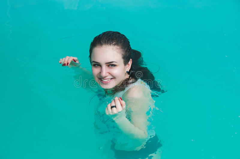 Young woman in the water pool. Young woman relaxing in the water stock image