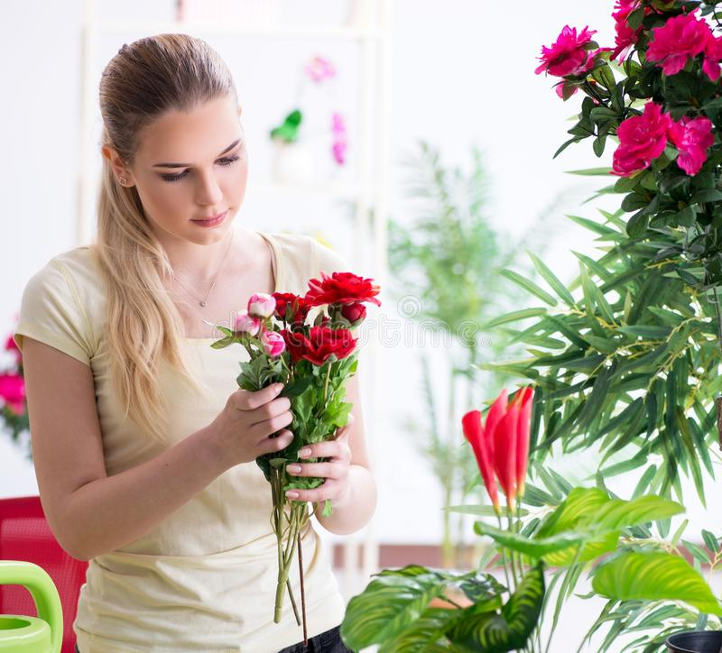 Young woman watering plants in her garden stock images