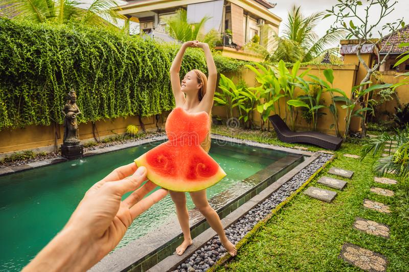 Young woman in a watermelon dress on a pool background. The concept of summer, diet and healthy eating royalty free stock images