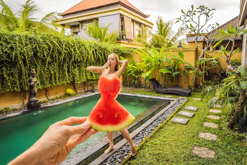 Young woman in a watermelon dress on a pool background. The concept of summer, diet and healthy eating royalty free stock photos