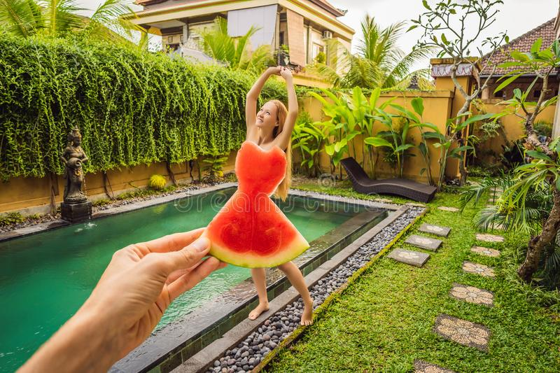 Young woman in a watermelon dress on a pool background. The concept of summer, diet and healthy eating stock images