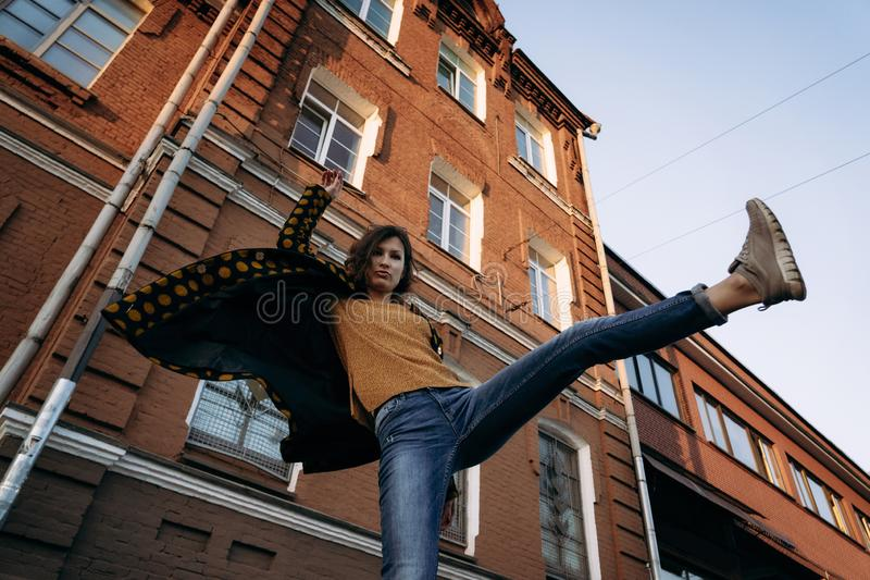 Young woman raises her leg up outdoor in evening. Young woman waves a hand raises her leg up outdoor in evening. Coat develops against brick wall. Low angle view royalty free stock photography