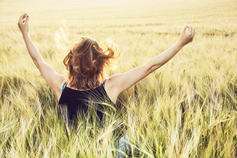 Young woman waving hands to the sun in the field by summer royalty free stock photography