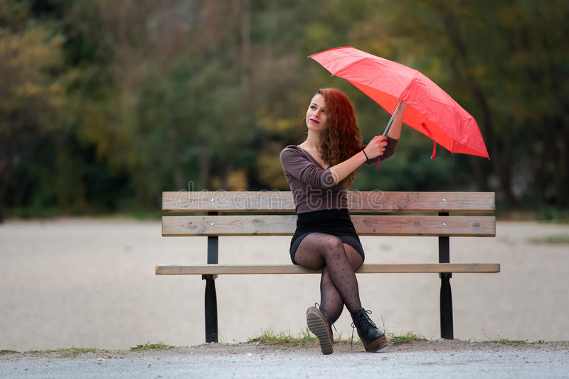 Young woman wear skirt sitting on bench holding a red umbrella stock photography