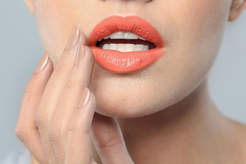Young woman wearing beautiful lipstick on gray background royalty free stock photography