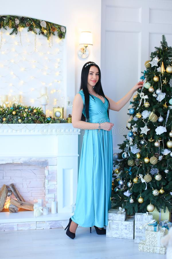 Young woman wearing blue dress standing near decorated fireplace and Christmas tree. stock images