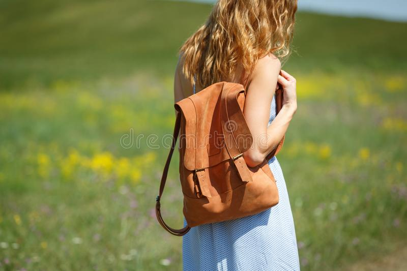 Young woman with a leather backpack in a summer field. Young woman wearing blue summer dress with a brown foxy leather backpack standing in a summer field stock photos