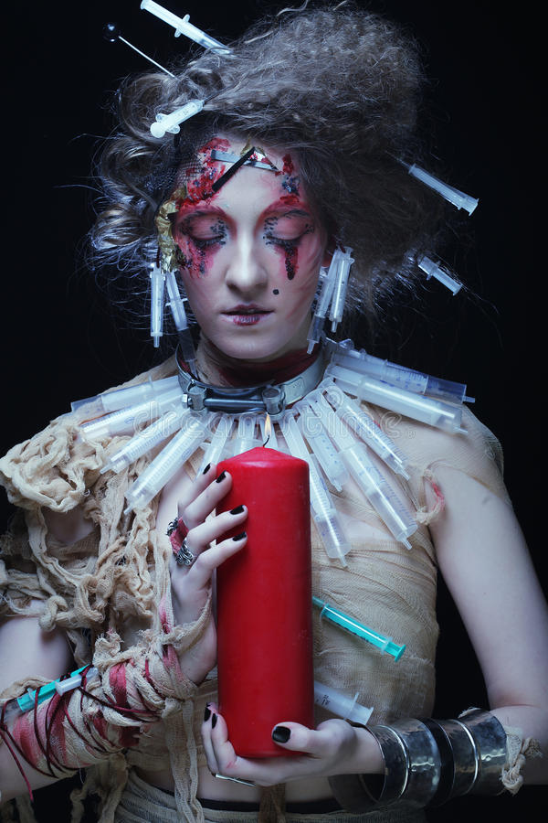 Young woman wearing carnival costume holding a candle. Young woman with bright make up wearing carnival costume holding a candle. Halloween picture stock photography