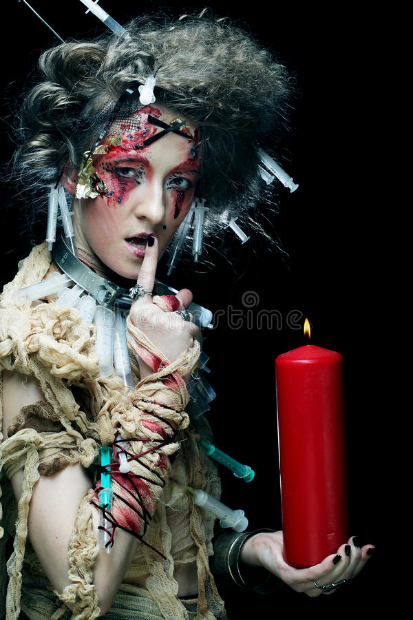 Young woman wearing carnival costume holding a candle. Young woman with bright make up wearing carnival costume holding a candle. Halloween picture stock image