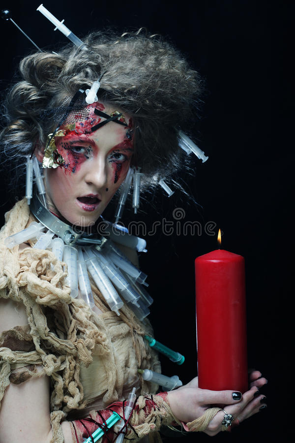 Young woman wearing carnival costume holding a candle. stock photo