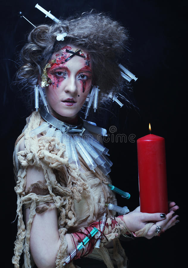 Young woman wearing carnival costume holding a candle. Young woman with bright make up wearing carnival costume holding a candle. Halloween picture royalty free stock photo