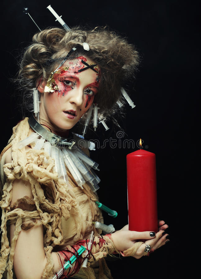 Young woman wearing carnival costume holding a candle. Young woman with bright make up wearing carnival costume holding a candle. Halloween picture royalty free stock photography