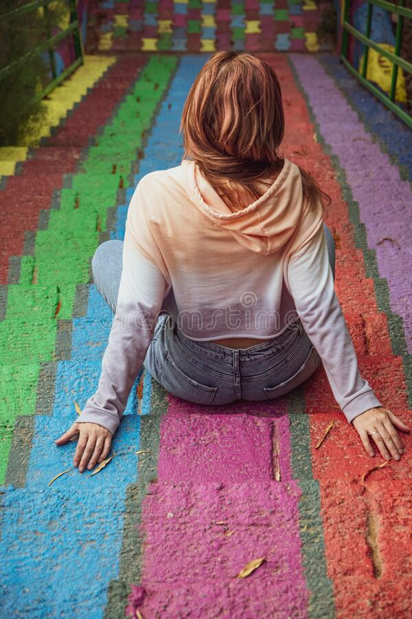 Free Young Woman Wearing Casual Clothes Sits Back To Camera On Rainbow Painted Stairs Stock Photos - 221292573