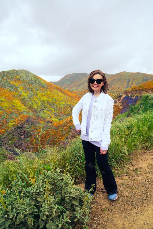 Young woman wearing casual white jean jacket and yoga pants poses on the trail at Walker Canyon during the California Poppy super. Bloom royalty free stock images