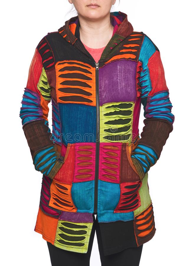 Young woman wearing coat of many colors hooded long patchwork jacket stock photo