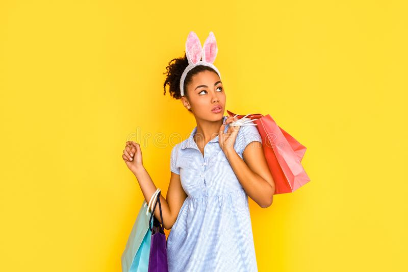 Shopping Concept. Young woman in cute dress and bunny ears standing isolated on yellow with bags looking aside curious stock photo