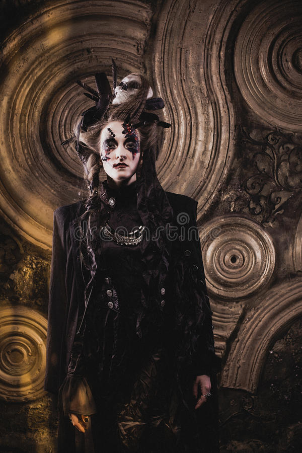 Young woman wearing dark costume. Bright make up and smoke- halloween theme. Young beautifull woman wearing dark costume. Bright make up and smoke- halloween stock photography