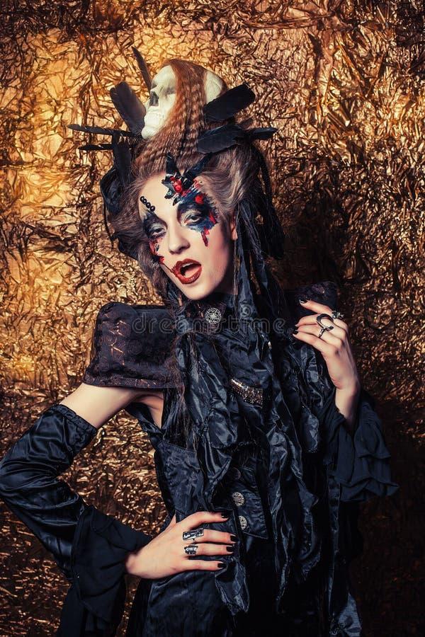 Young woman wearing dark costume. Bright make up and smoke- halloween theme. Young beautifull woman wearing dark costume. Bright make up and smoke- halloween stock photo
