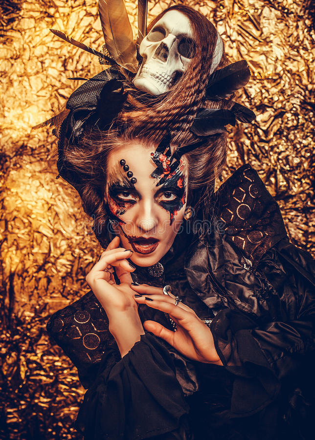 Young woman wearing dark costume. Bright make up and smoke- halloween theme. Young beautifull woman wearing dark costume. Bright make up and smoke- halloween royalty free stock images