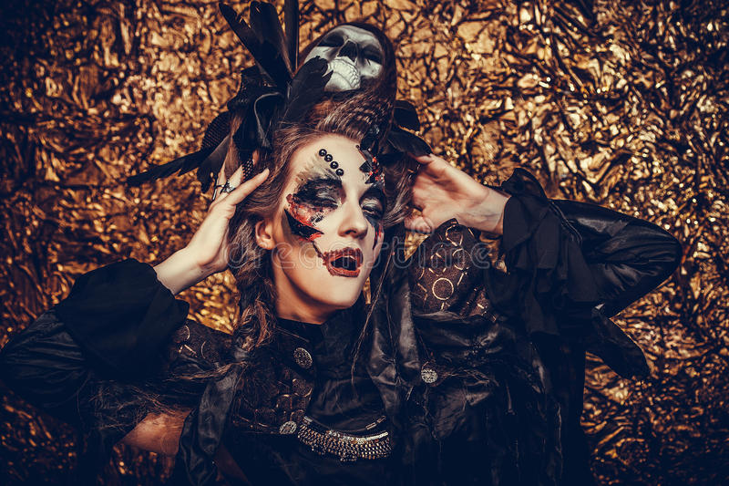 Young woman wearing dark costume. Bright make up and smoke- halloween theme. Young beautifull woman wearing dark costume. Bright make up and smoke- halloween royalty free stock photography