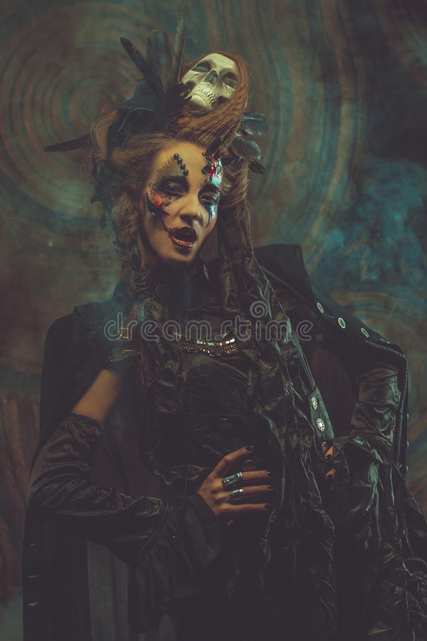 Young woman wearing dark costume. Bright make up and smoke- halloween theme. royalty free stock photography