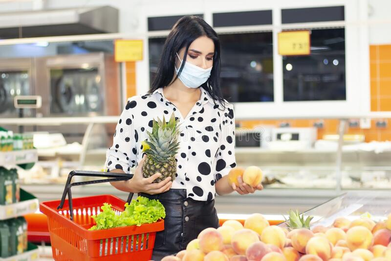 Young woman wearing disposable medical mask shopping in supermarket royalty free stock photo